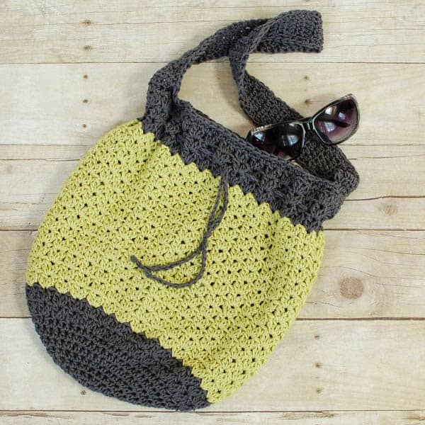 amazing crochet market bags, with two colors, laying on the floor with sunglasses
